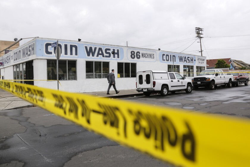 An LAPD detective walks toward a laundromat on the 7300 block of South Figueroa Street in South L.A., where the body of a man with gunshot wounds was discovered, on April 9, 2016.