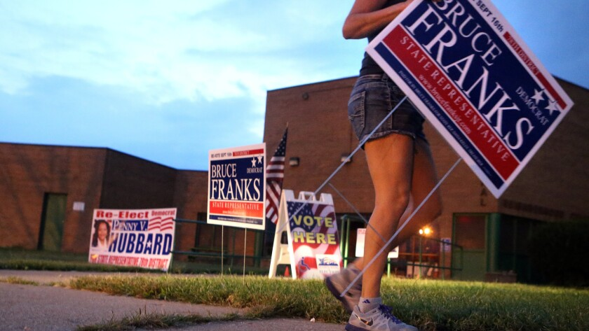 A supporter plants signs for a Missouri state representative candidate last month in St. Louis. A judge ordered the a redo of the election for the state's 78th District after allegations of improper counting of absentee ballots.