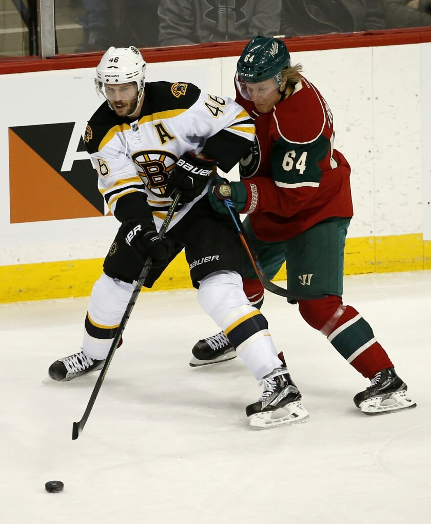 Boston Bruins center David Krejci (46), of the Czech Republic, passes the puck to a teammate in front of  Minnesota Wild center Mikael Granlund (64), of Finland, during the first period of an NHL hockey game in St. Paul, Minn., Saturday, Feb. 13, 2016. (AP Photo/Ann Heisenfelt)