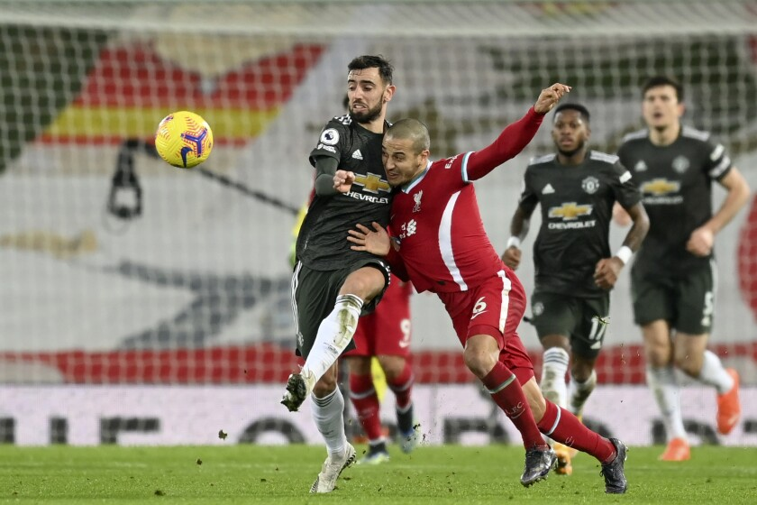 Liverpool's Thiago vies for the ball with Manchester United's Bruno Fernandes, left, during the English Premier League soccer match between Liverpool and Manchester United at Anfield Stadium, Liverpool, England, Sunday, Jan. 17, 2021. (Michael Regan/Pool via AP)