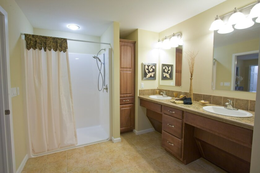 This age-friendly bathroom has such features as a roll-in shower, handheld shower head and recessed cabinets under the sinks to allow for wheelchair access.