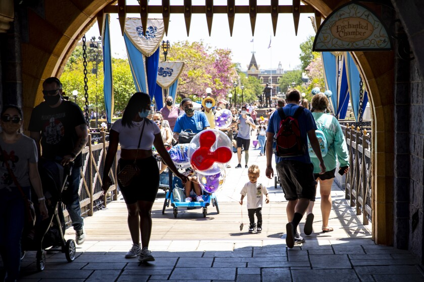 People walk under a gate at Disneyland in Anaheim.