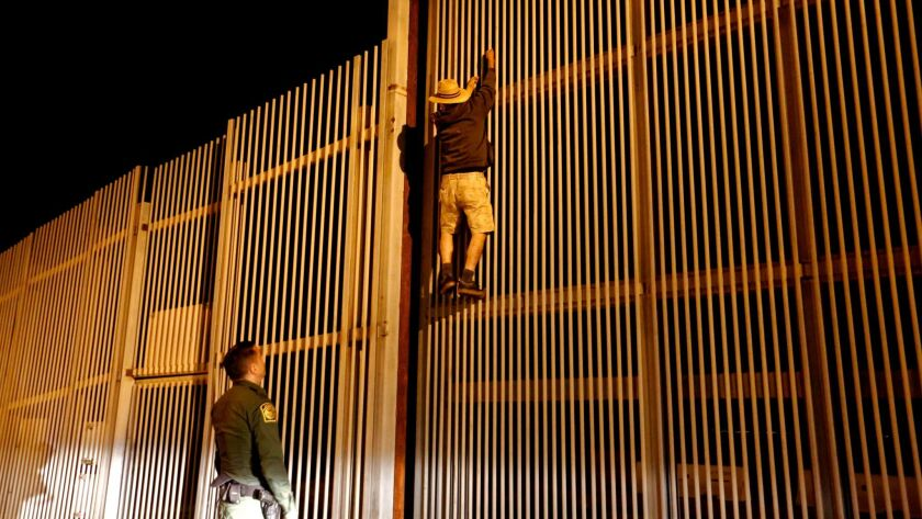 Border Patrol Agent Eduardo Olmos apprehends a Mexican immigrant trying to cross the U.S.-Mexico border in San Diego.