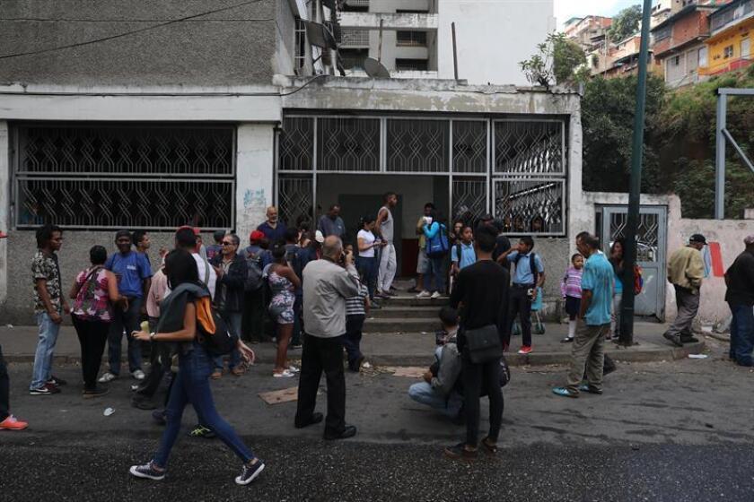 Personas se concentran este jueves en el lugar donde yace el cuerpo de un hombre que regresaba de hacer una diligencia cuando se dio cuenta de los enfrentamientos con la Guardia Nacional y al correr fue impactado por una bala durante las protestas de ayer, en Caracas (Venezuela). EFE