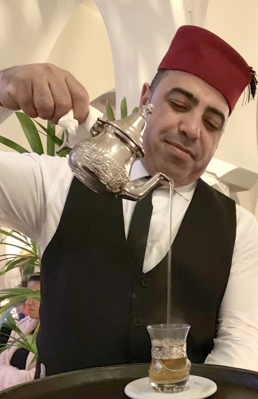 Rashid, our fez-topped waiter, pours sweet mint tea after dinner at Rick's Cafe in Casablanca.