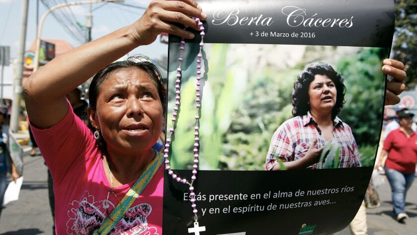 FILE - In this March 16, 2016, file photo, a woman holds up a poster with a photo of slain environme