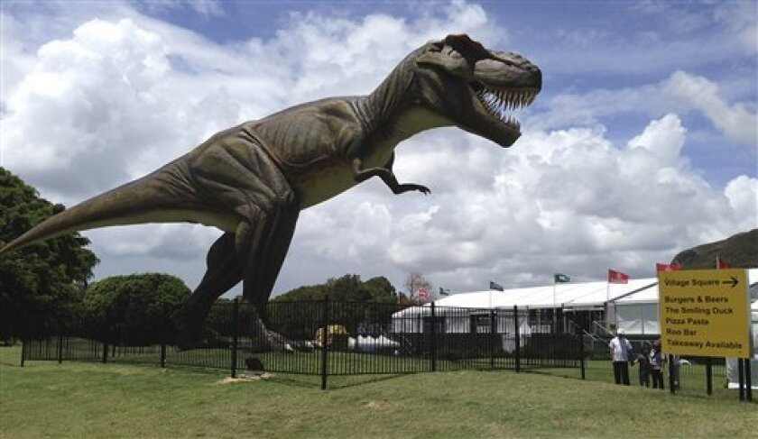 People stand near an eight-meter (26-foot) replica of a tyrannosaurus rex standing between the 9th green and the 10th tee at the Sunshine Coast resort course in south Queensland, Australia, Tuesday, Dec. 11, 2012. The Australian PGA will move from its Sunshine Coast resort course location after 11 years, with blame lying indirectly, on the new robotic dinosaur. (AP Photo/Dennis Passa)