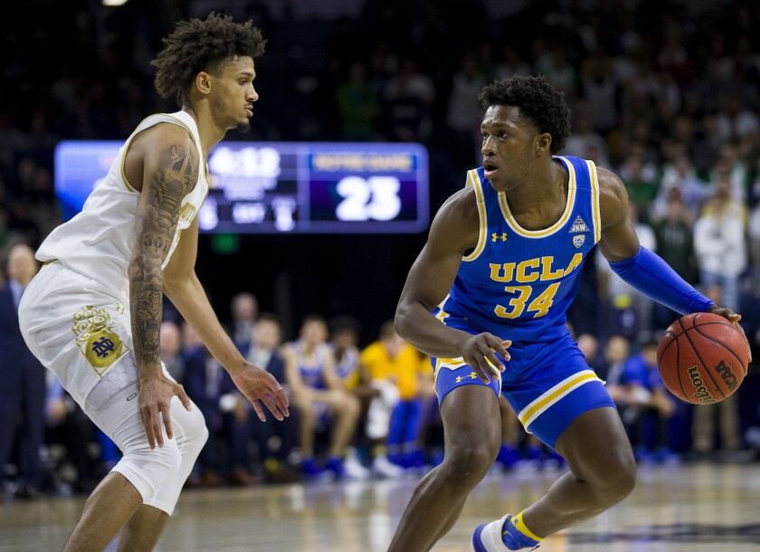 UCLA's David Singleton is pressured by Notre Dame's Prentiss Hubb during the first half Saturday.