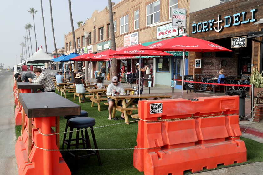 Customers sit in an outdoor dining area.
