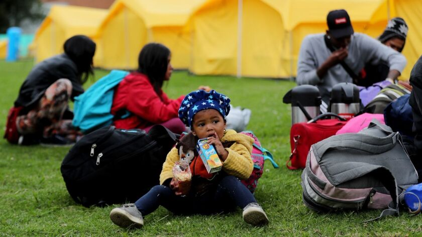 A Venezuelan child drinks juice after being moved by Colombian authorities to a camp in Bogota on Tuesday.