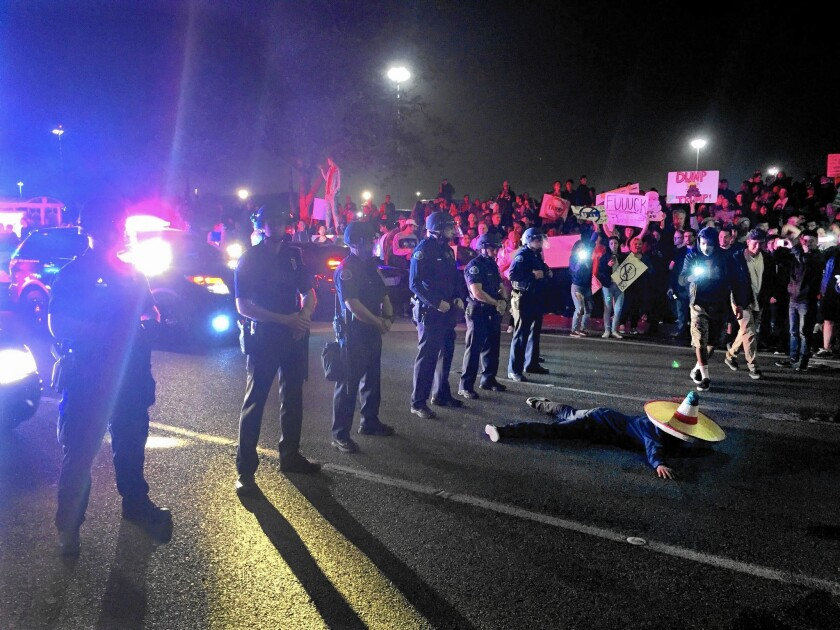 A demonstrator against Donald Trump lies before a line of Costa Mesa police officers at the intersection of Fair Drive and Fairview Road near the Pacific Amphitheater, where the candidate's freewheeling speech was cheered by more than 8,000 supporters.