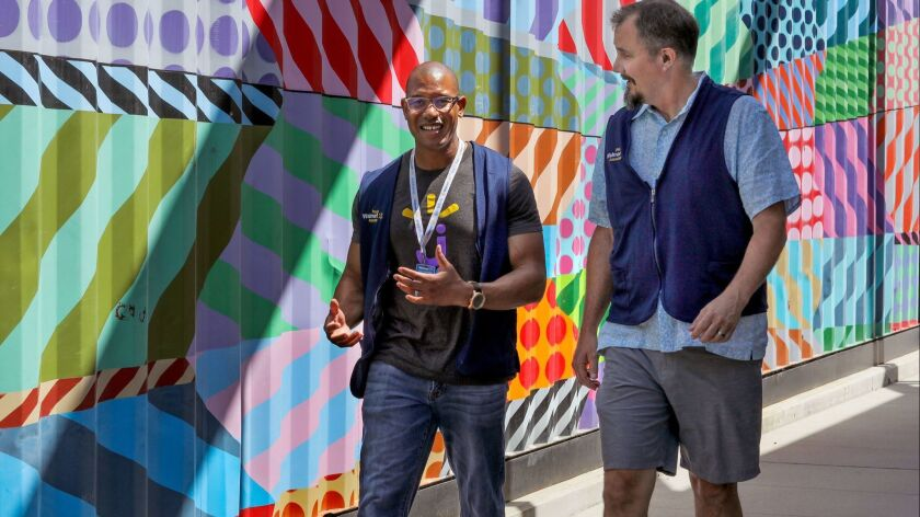 Claude Jones, left, and Bob Lowell, both Senior Directors of Engineering for Walmart Labs, walk past the rear of the Copa Vida Cafe at the Make campus in Carlsbad where Walmart Labs' San Diego area