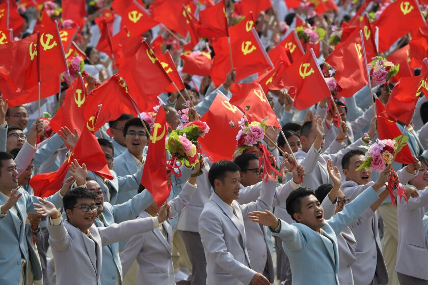 People wave Communist Party flags during a military parade in Tiananmen Square in Beijing on Oct. 1, 2019, to mark the 70th anniversary of the founding of the People's Republic of China.