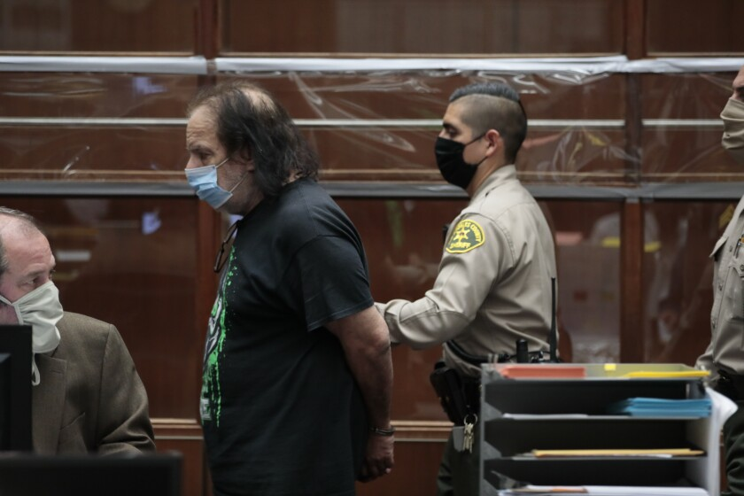 Adult film star Ron Jeremy, charged with four counts of sexual assault, leaves a Los Angeles County courtroom in handcuffs