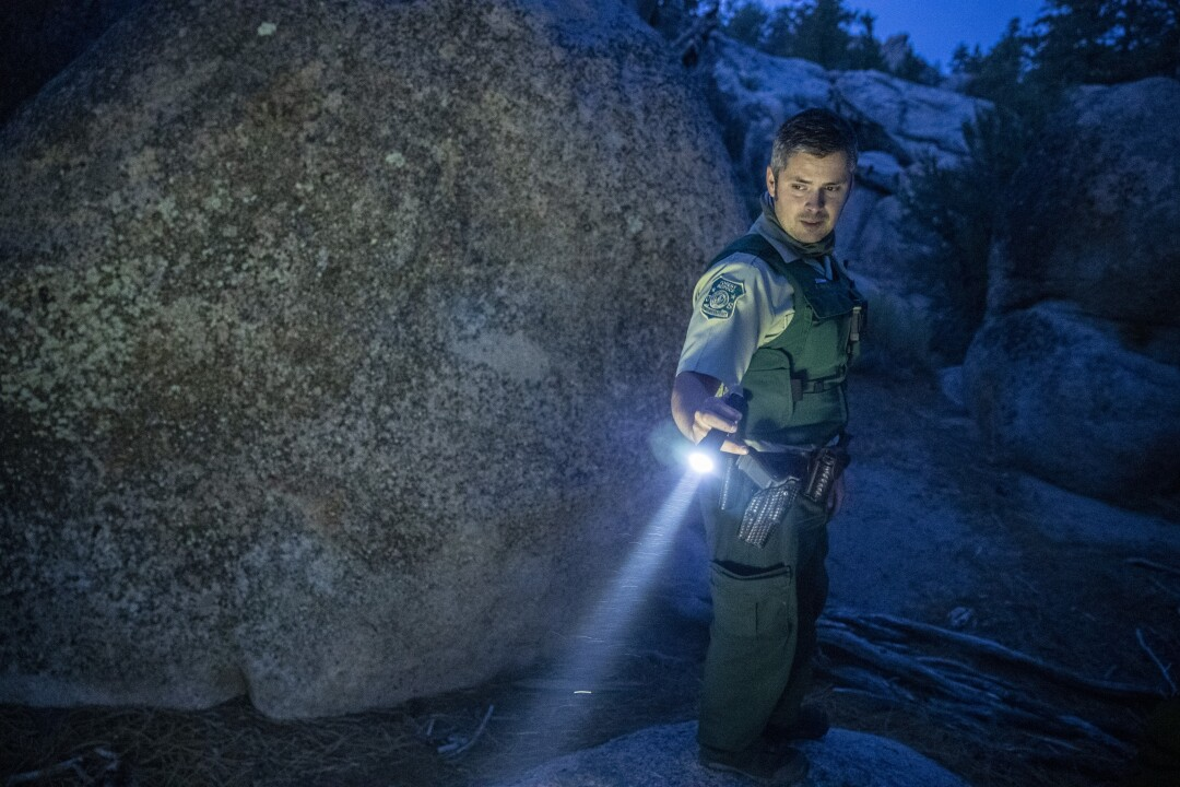 Forest service law enforcement officer Tyler Smith looks for evidence of illegal camping while on patrol