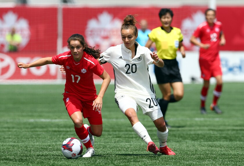 Canada's Jessie Fleming, left, controls the ball ahead of Germany's Lina Magull during an international friendly match in June 2018.