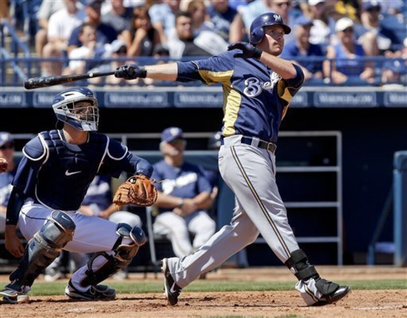 Milwaukee Brewers' Mat Gamel hits a grand slam home run against the San Diego Padres in the third inning of a spring training baseball game Saturday, March 31, 2012 in Peoria. Ariz.  It was the  first of two home runs by Gamel.The Padres catcher is John Baker. (AP Photo/Lenny Ignelzi)