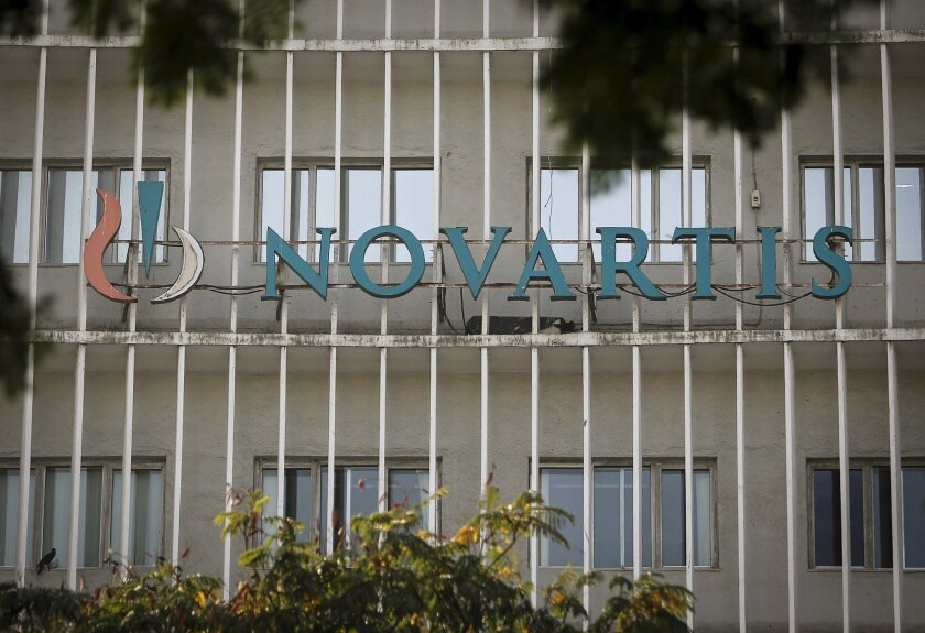 A Novartis logo is pictured on its headquarters building in Mumbai The drug giant is working with Qualcomm Life to develop an Internet connected inhaler.