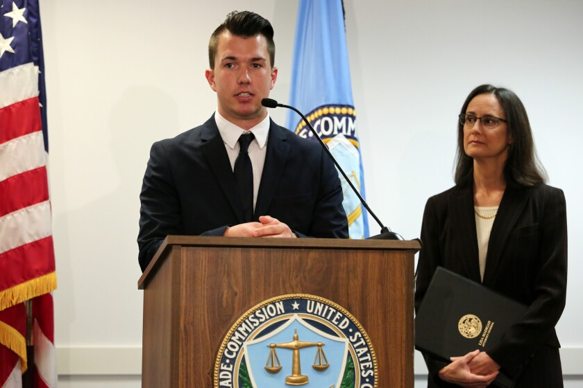 Josh Rozman, of Tampa, Fla., an alleged victim of a Chicago-area debt collection operation that authorities said coerced consumers into paying payday loan debts they did not owe, speaks at a news conference last year. Illinois Attorney General Lisa Madigan on Tuesday announced a settlement in the case.