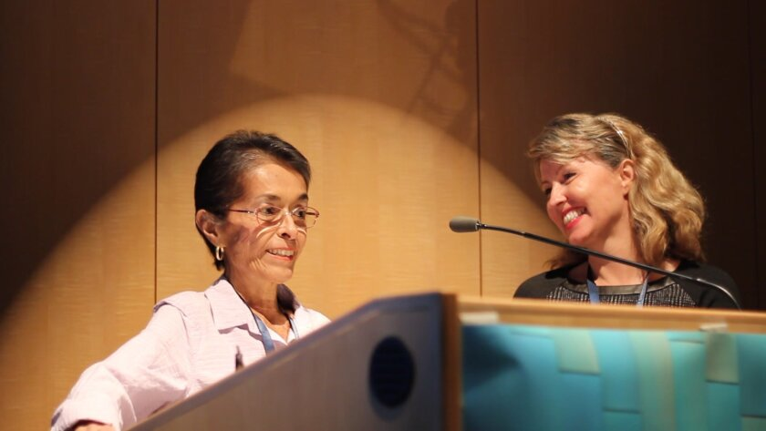 Theresa Blanda speaks about her experience battling cancer with the help of Dr. Catriona Jamieson, smiling on the right.
