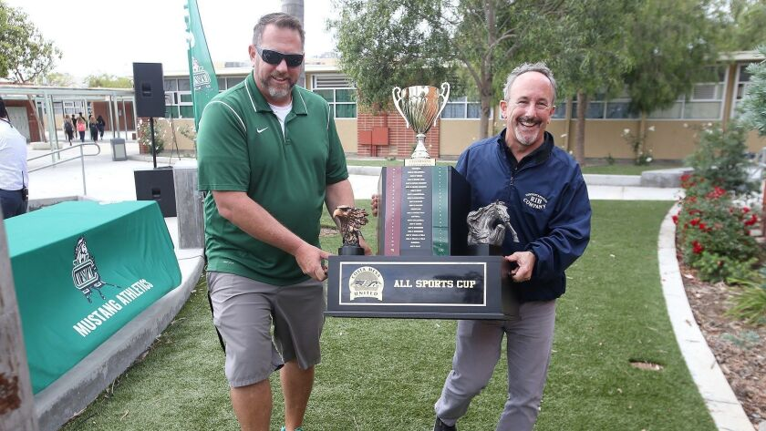 Athletic director Mike Ofer and Newport Rib Company's John Ursini, carry the All-Sports Cup Trophy