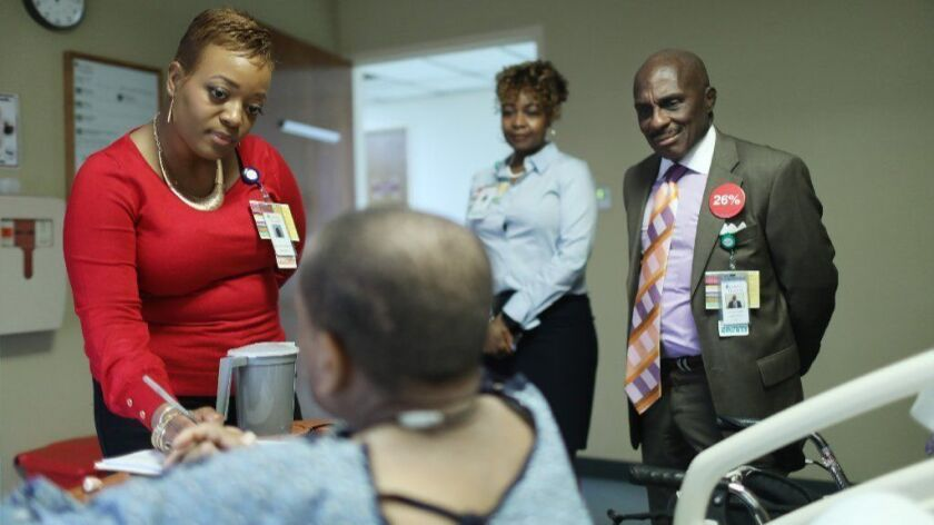 Angela K. Waller, left, director of community engagement and strategic partnerships at Loretto Hospital, speaks with a patient as hospital CEO George N. Miller Jr. and Tanesha Daniels, chief experience officer, listen during a team visit with patients and staff, March 7, 2019.