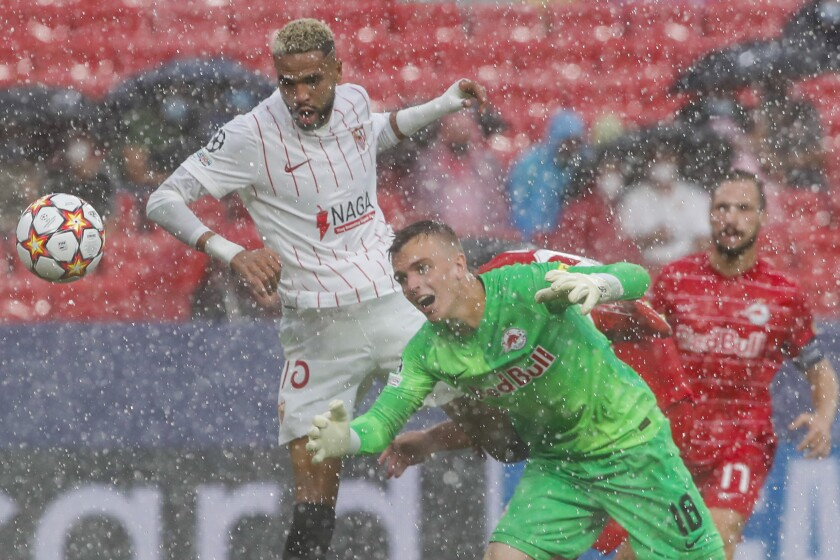 Salzburg's goalkeeper Philipp Koehn, right, tries to save a ball next to Sevilla's Youssef En-Nesyri during the Champions League, Group G soccer match between Sevilla and Salzburg at the Ramon Sanchez Pizjuan stadium in Seville, Spain, Tuesday, Sept. 14, 2021. (AP Photo/Angel Fernandez)