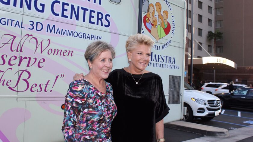 At the symposium, Komen San Diego CEO Laura Farmer Sherman (left) and broadcast journalist Joan Lunden stand in front of the mobile mammography coach, an RV painted pink and equipped with 3D mammography equipment. More details at komensandiego.org