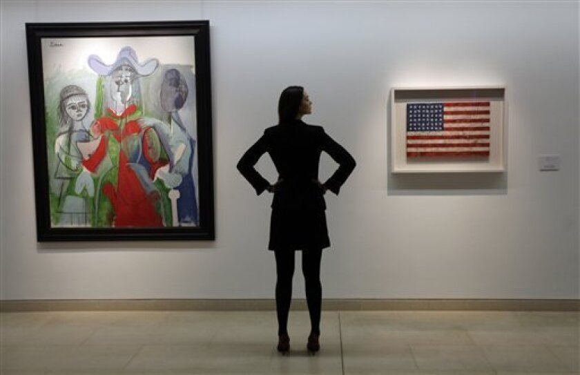 """An auction house worker poses for photographers between a 1961 Pablo Picasso painting, left, and an encaustic Stars and Stripes painting entitled 'Flag' , right, made between 1960-1966 by U.S. artist Jasper Johns, in central London, Friday, Feb. 5, 2010. Four pieces from the collection of late Michael Crichton, the mega-selling thriller writer behind 'Jurassic Park', and TV series """"ER,"""" and a passionate art collector went on display in London before being auctioned by Christie's auction house in New York on May 11. The sale also includes works by Robert Rauschenberg and Roy Lichtenstein and the auction house is valuing them collectively at 20 million british pounds (some 32 US million dollars). (AP Photo/Lefteris Pitarakis)"""