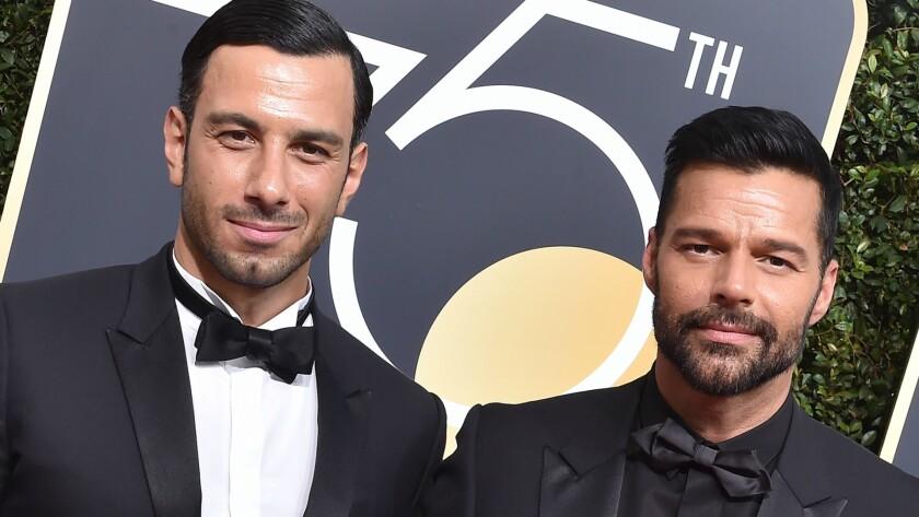 Ricky Martin (derecha) y su flamante esposo a su paso por la alfombra roja de los Globos de Oro, el domingo pasado.