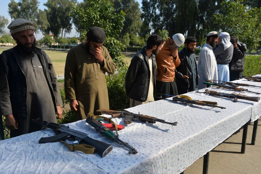 Former Afghan Taliban fighters stand next to weapons before handing them over.