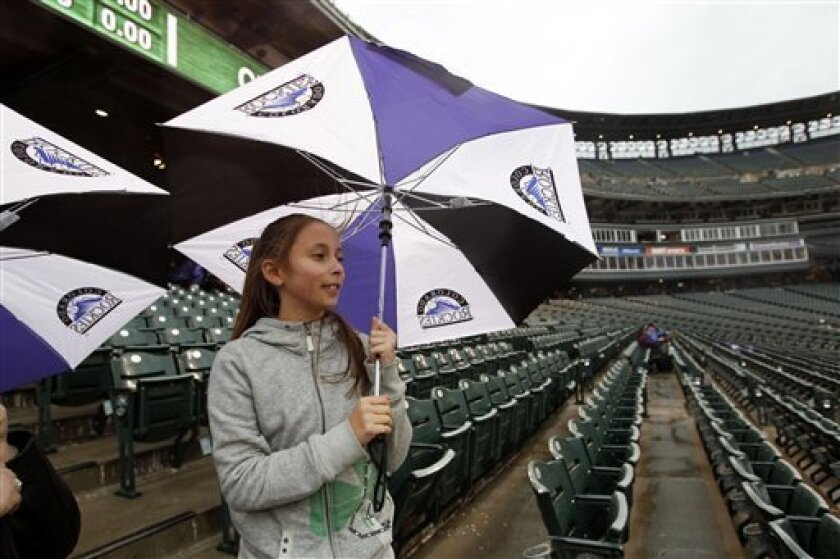 Nine-year-old Katie Stevens, of Denver, uses her umbrella for cover as a light rain envelops Coors Field in Denver before the Colorado Rockies host the Arizona Diamondbacks in a baseball game on Saturday, April 14, 2012. The start of the game had been delayed because of the rainy, blustery weather. (AP Photo/David Zalubowski)