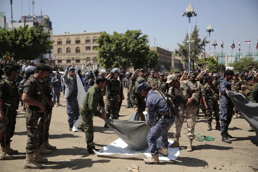 Policías cargan el cuerpo de un hombre, condenado por su participación en el asesinato del oficial hutí Saleh al-Samad