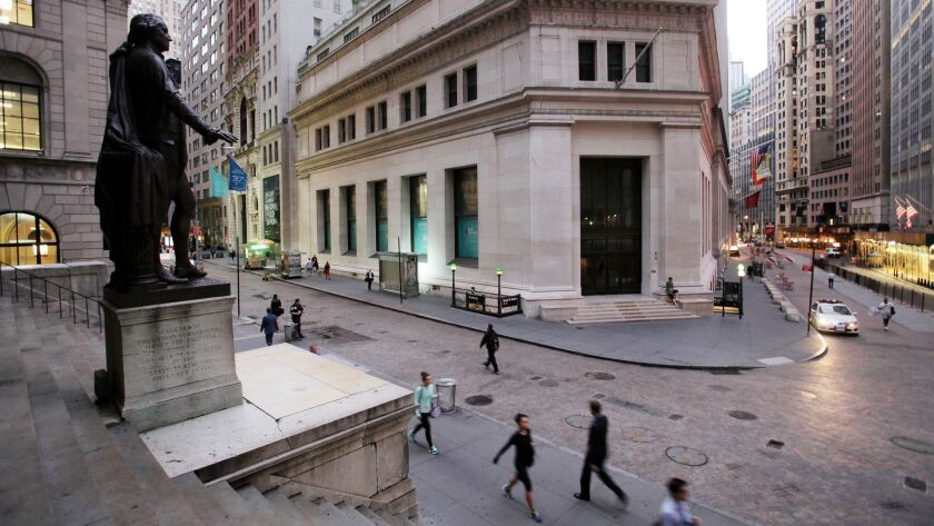 People walk to work on Wall Street in New York beneath a statue of George Washington in 2014.