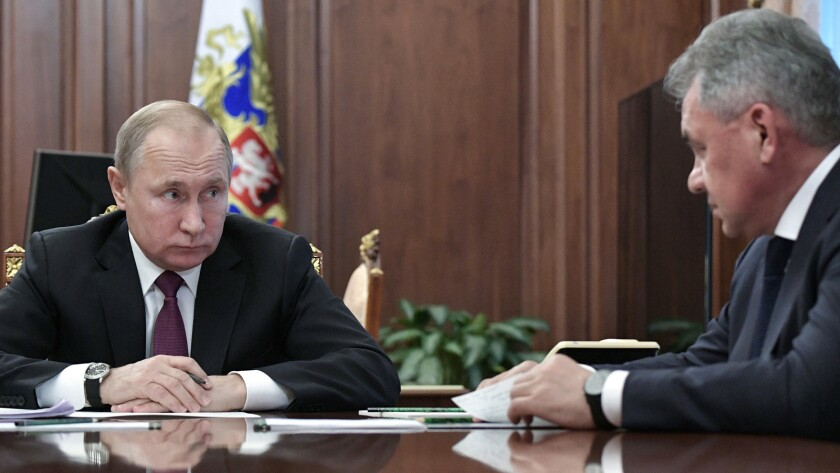 Russian President Vladimir Putin, left, speaks to Defense Minister Sergei Shoigu in the Kremlin on Saturday.
