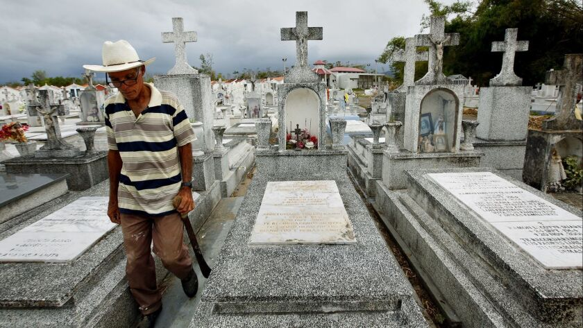 Heriberto Riveiro passes the grave of Leohermanijildo Cotte, whose death has been blamed on Hurricane Maria because it knocked out the power to his oxygen pump.