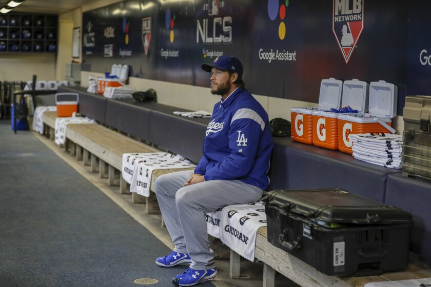 Dodgers pitcher Clayton Kershaw sits alone in the dugout for a few moments before heading to the outfield for pregame warmups in Game 1 of the National League Championship Series at Miller Park.