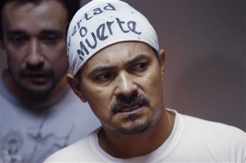 """Imprisoned landless farmer leader Ruben Villalba, who is on his 17th day of a hunger strike, wears a sign on his head that reads in Spanish """"Freedom or death"""" as he attends his pre-trial hearing at court in Col. Oviedo city, Paraguay, Thursday, Feb. 14, 2013. Behind is fellow farmer Nestor Castro, who is also on a hunger strike. The prosecutor says he has no physical evidence showing who killed six police officers during a bloody land dispute that prompted the downfall of Paraguayan President Fernando Lugo. He says he didn't even try to determine who killed 11 farm workers who also died when the bullets started flying. Villalba and Castro are on hunger strike to protest their eight month imprisonment without formal charges. (AP Photo/Jorge Saenz)"""