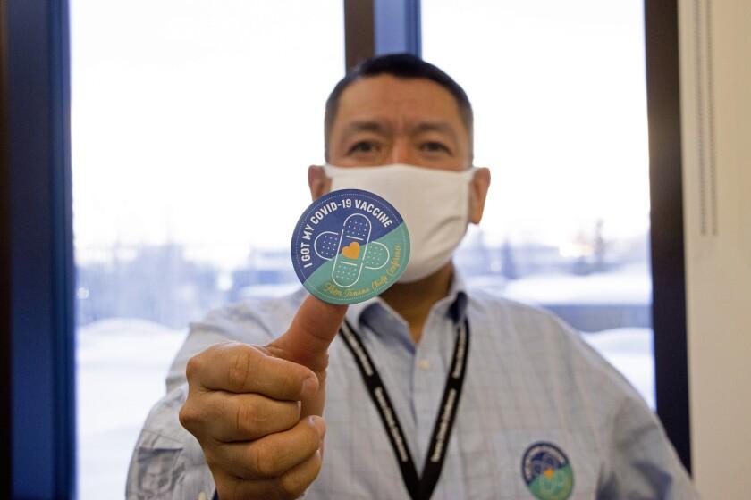 PJ Simon displays a COVID-19 vaccination sticker