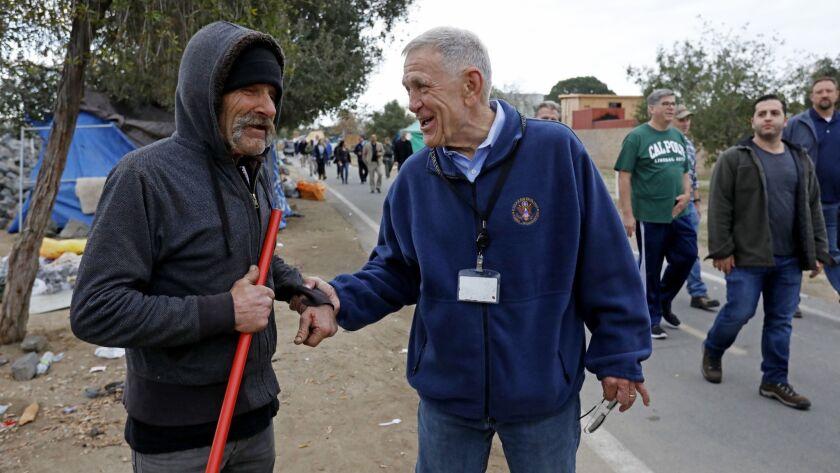 U.S. District Judge David Carter, right, greets Eddie S., 63, a homeless man, on Feb. 14, 2018.