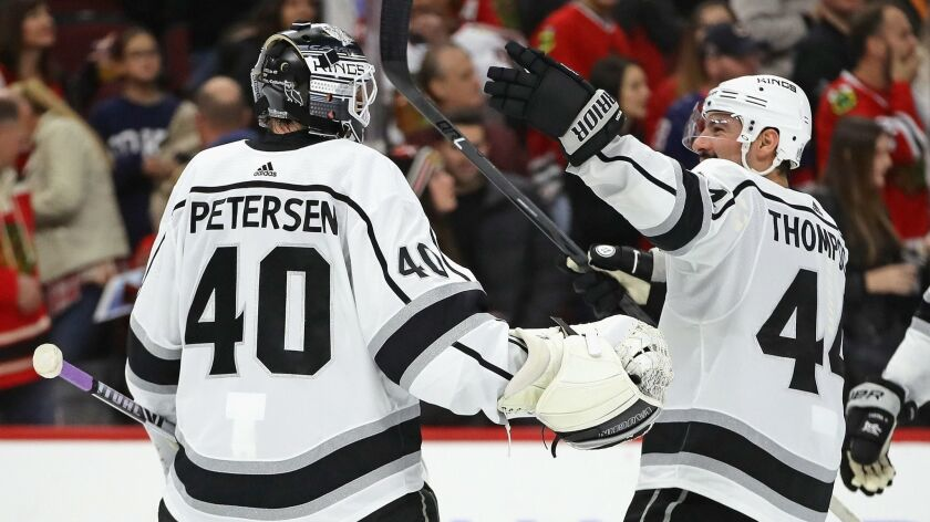 Kings' Nate Thompson (44) skates up to congratulate Calvin Petersen (40) after a win over the Chicago Blackhawks at the United Center on Friday in Chicago.