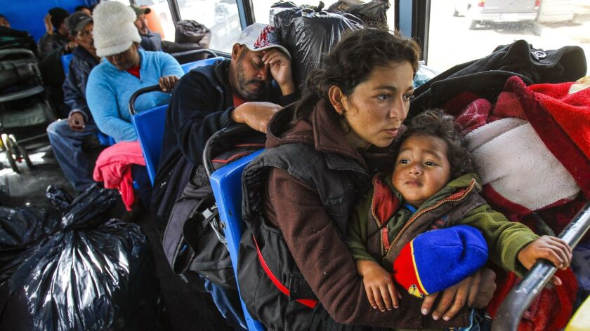 Jamileth Mejia, 30, from Honduras, holds her daughter Emily, 3, as they and other Central American migrants, who were staying at the Benito Juarez sports complex shelter, ride a bus to the newly set up El Barretal shelter eleven miles away in Tijuana on Friday.