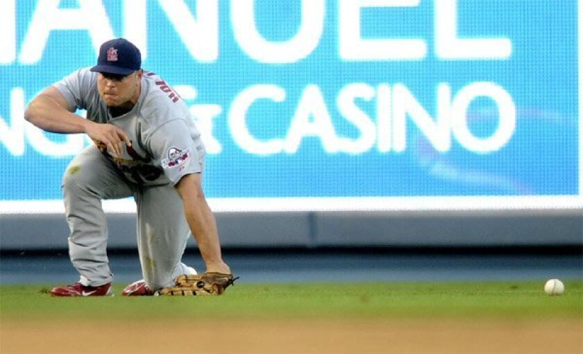 Left fielder Matt Holliday fails to glove James Loney's sinking liner for a ninth-inning error that doomed the Cardinals. (Wally Skalij / Associated Press)