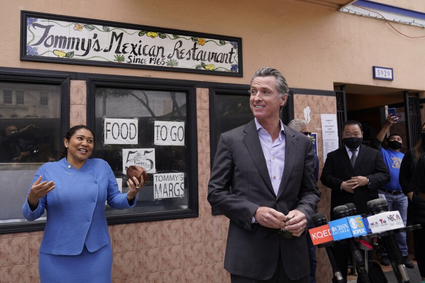 California Gov. Gavin Newsom prepares to speak at a news conference about relief for restaurants as San Francisco Mayor London Breed laughs and looks on outside Tommy's Mexican Restaurant in San Francisco, on Thursday, June 3, 2021. The governor offered his support for the extension and expansion of outdoor dining and takeout cocktails. (AP Photo/Eric Risberg)