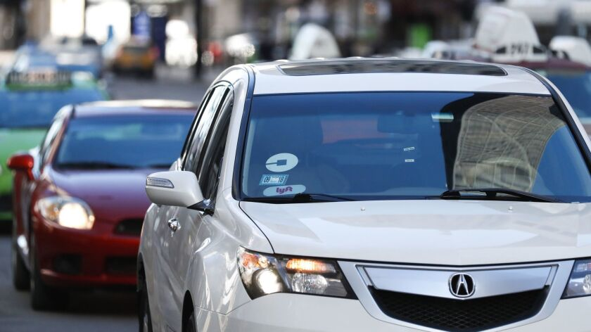 A vehicle with Uber and Lyft stickers drives on North Michigan Avenue in Chicago on Feb. 1.