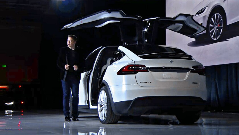 Tesla CEO Elon Musk shows off one of the first Model Xs to be delivered to customers.