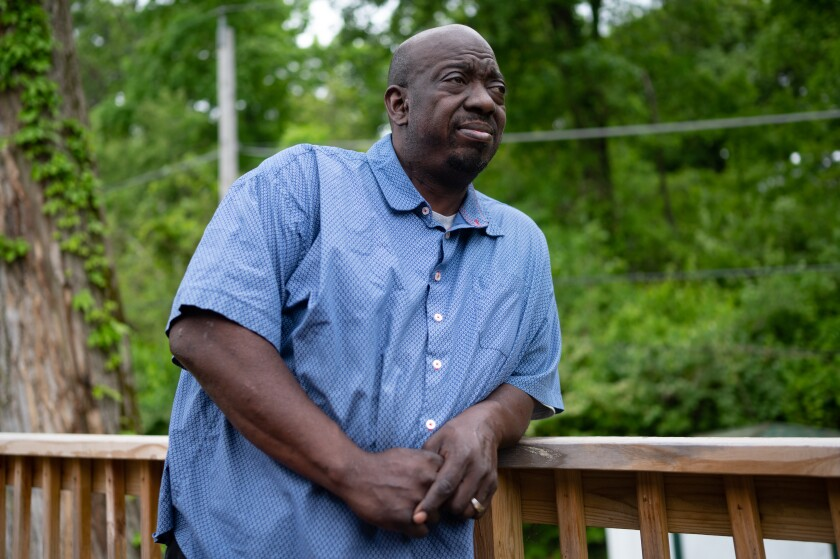 A man in a blue shirt stands against a railing on his deck outside.