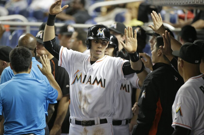 Miami Marlins' Christian Yelich, center, is congratulated by teammates after scoring on a sacrifice fly by J.T. Realmuto during the third inning of a baseball game against the Pittsburgh Pirates, Thursday, June 2, 2016, in Miami. (AP Photo/Wilfredo Lee)