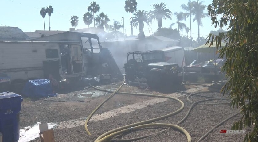 Firefighters battle a blaze Friday that burned several vehicles and at least two structures, including a garage and home