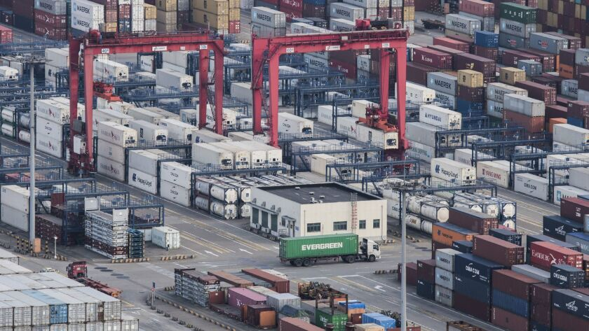 """How much is really """"made in China""""? A cargo truck drives amid stacked shipping containers at Shanghai port."""